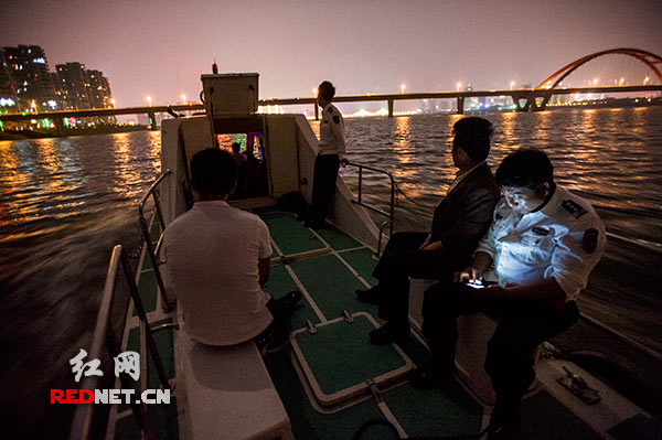 Completed another night patrol the river, fishery inspectors return sail boats illuminated the city of Changsha.