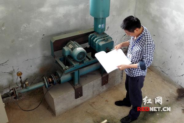 在湖南中和制药有限公司,执法人员检查污水处理站,查看污水处理设施运行台账。