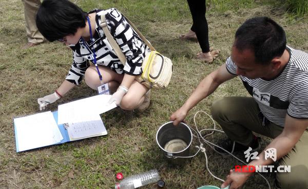 在湖南中和制药有限公司,对污水排放总排口进行采样,执法人员现场记录。