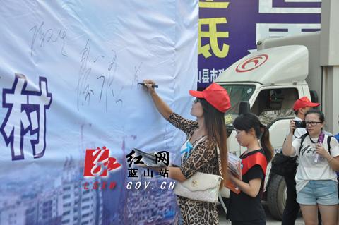 志愿者,群众在禁毒宣传条幅上签名
