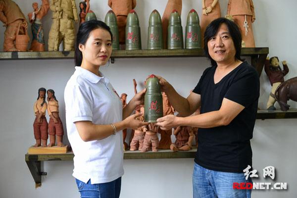 """报道团记者将""""胜利的子弹""""交给雕塑家肖小裘。"""