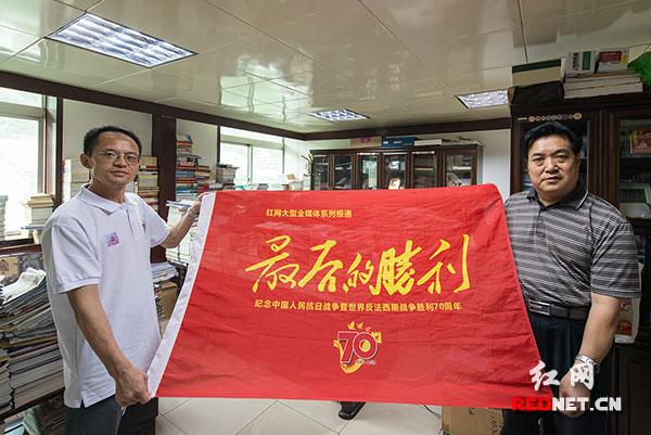 """郝凤年教授接受报道组采访并与""""最后的胜利""""旗帜合影"""