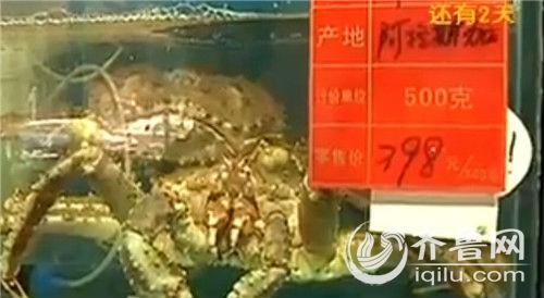 店老板从水箱中捞出一只中等大小的帝王蟹,在电子称上显示重量为4.5千克,也就是9斤。(视频截图)