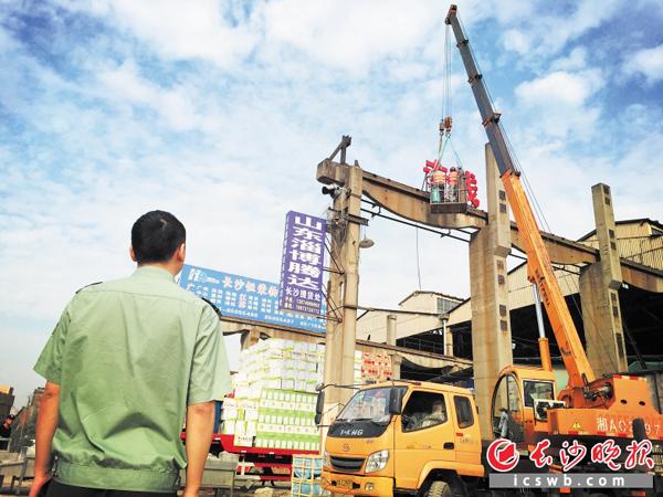 借助高高的塔吊,工人们正在拆除房顶上物流的招牌