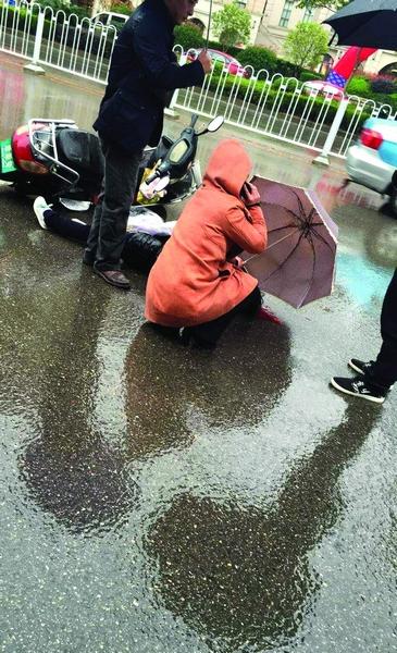 白色捷达车肇事逃逸 好心路人为车祸伤者撑伞