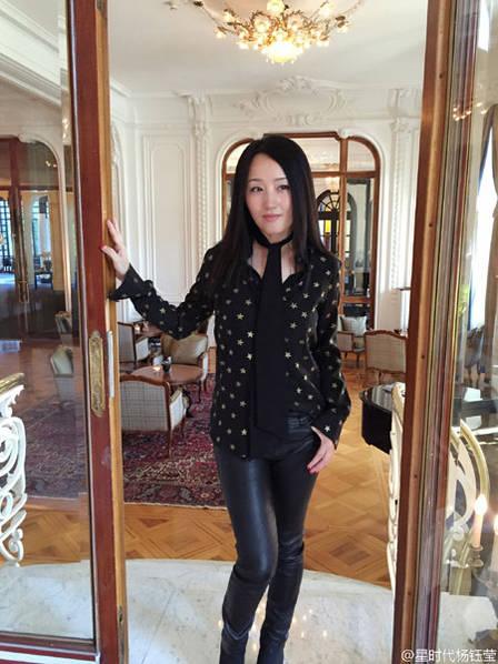 照片中,杨钰莹长发披肩,穿白色收腰风衣,身处充满圣诞氛围的饼屋前