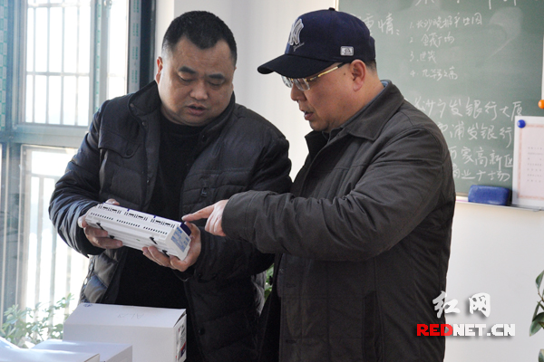 李宏(左)向邹明(右)介绍公司产品。