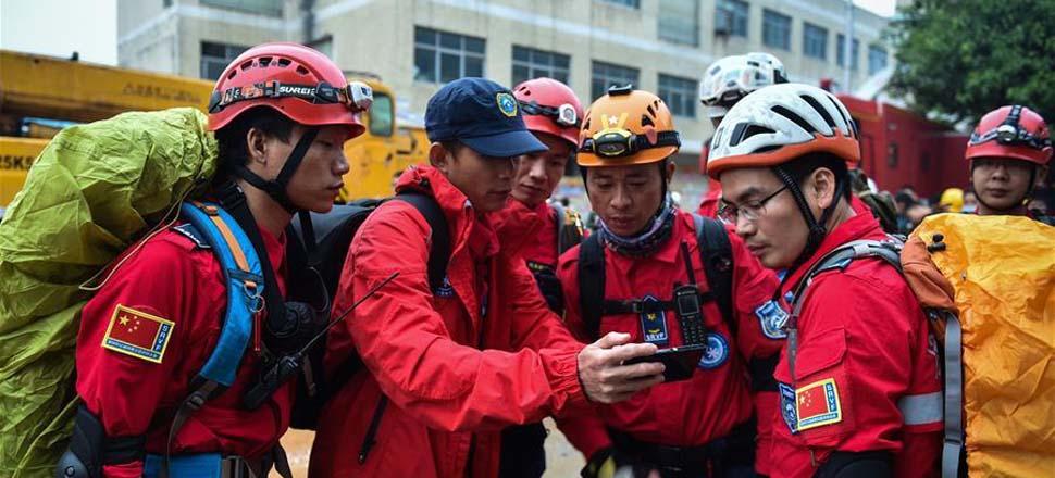 12月20日,深圳山地救援队的成员在事故现场商议救援方案。