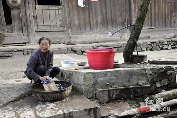 村里通了自来水后,六十多岁的鲁冬翠可以在自家门口洗衣服了。