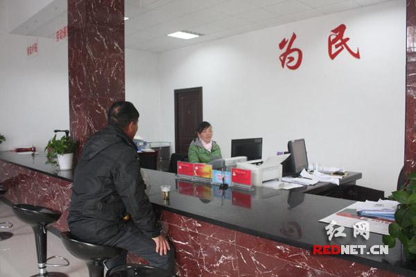 村民陈迪辉在便民服务中心,一边喝着热茶,一边在办事。