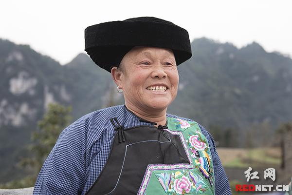 63岁的石大姐和邻居们在村口即兴喊了一段苗歌。7岁的孙女儿告诉时刻新闻记者,奶奶唱的是现在的好生活,高兴的意思。
