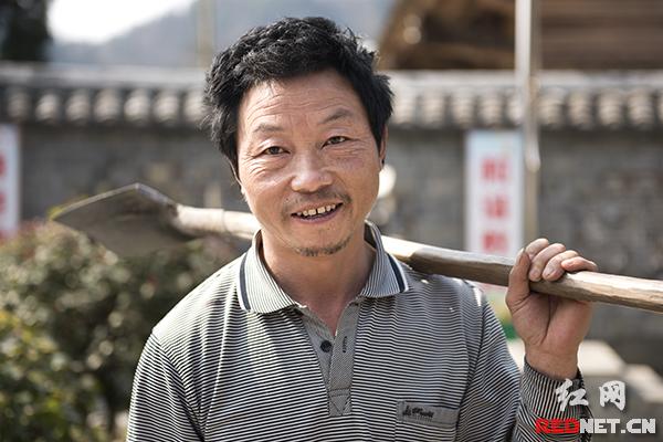 """45岁的刘清长家就住在十八洞小学旁边。快要开学了,刘清长主动来到校园里义务打扫卫生。去年,十八洞小学改建成了砖房,砌上了围墙,校园里还种上了桂花树。和以前的老木房相比,新校园别致雅静,""""应该好好珍惜""""。"""