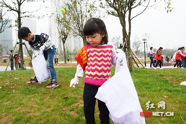 佩戴志愿袖章的小朋友提着垃圾袋捡垃圾。