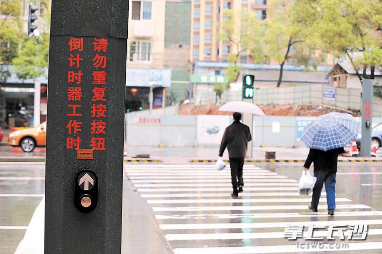 图为市民借助行人过街触控式信号灯在雨中从容过马路.