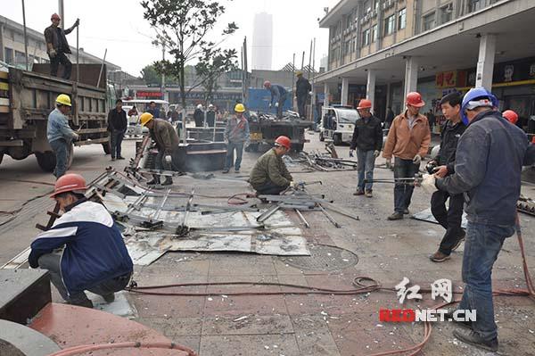 拆除工作人员正在清理现场,将拆除物运走。