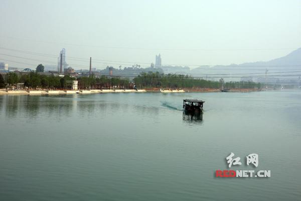 资兴市东江湾水面清澈,一艘打捞船正在进行垃圾打捞。
