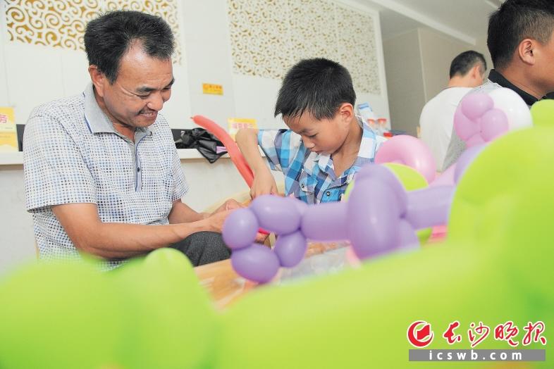 卜劲文)10岁的儿子折出魔术气球送给父亲;3岁的女儿自制贺卡献给爸爸.