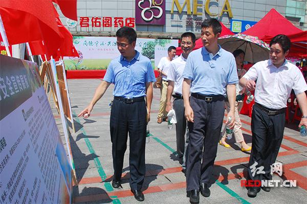 湖南省粮食局党组成员、副局长石少龙(前排左二)正在观看活动现场的食品安全宣传展板。