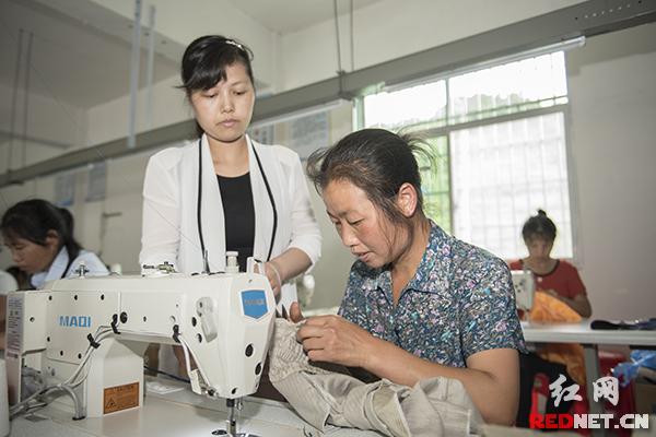 湖南芷江三道坑镇五郎溪村,刚刚创办的五郎溪服装厂,从外地返乡的妇女正在学习缝纫技术。