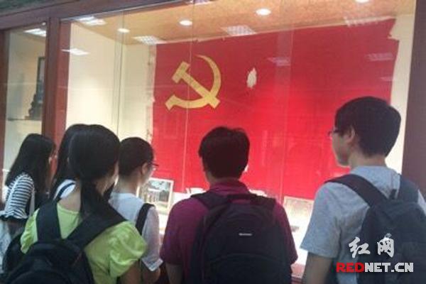观众在展出的中国共产党党旗前。