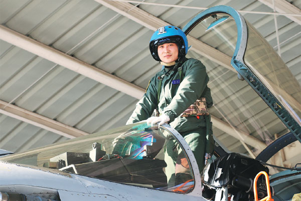 Pilot Zhang Chao poses for a photo before flying a J-15 Flying Shark fighter jet. The 29-year-old lieutenant commander died in April during a routine training exercise. (Photo provided to China Daily)