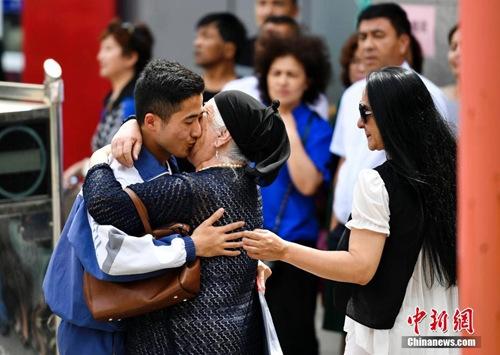 6月7日,2017年全国高考首日,新疆乌鲁木齐市高级中学考点,一位老者激动地拥吻刚刚参加完语文科目考试的考生。 中新社记者 刘新 摄