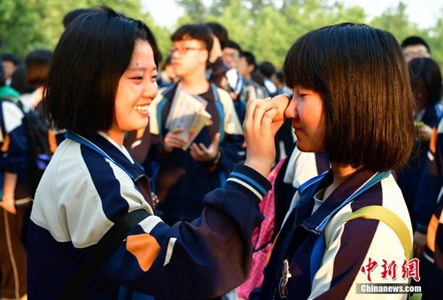 6月7日,在河北石家庄45中,参加高考的女学生正用鸡蛋帮同学敷脸放松面部神经。当日,为期两天的2017年中国高考正式拉开大幕,共有940万名考生参加考试。 中新社记者 翟羽佳 摄