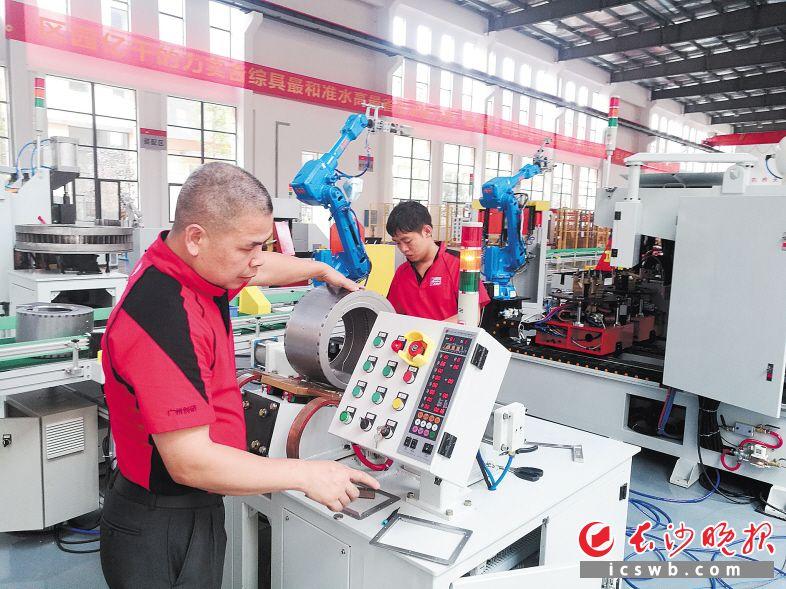 湖南创研厂房内,庞国森师傅在调试智能机器设备。他来自广东,技术精湛,工作认真。长沙晚报记者 王斌 摄