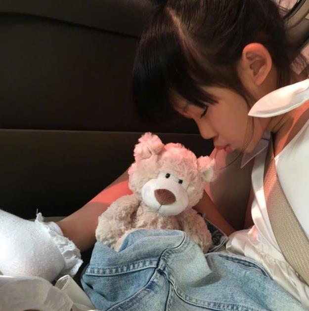 照片中,贝儿扎着高高的丸子头,抱着可爱的小熊娃娃,盘腿坐在车上睡着
