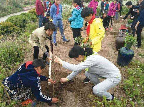 翁丽芬与孩子们一起植树