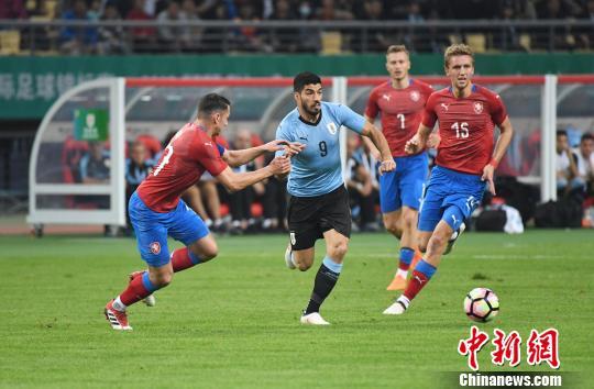 图为乌拉圭球员苏亚雷斯(蓝衣)在捷克队球员的防守中试图突围。俞靖 摄