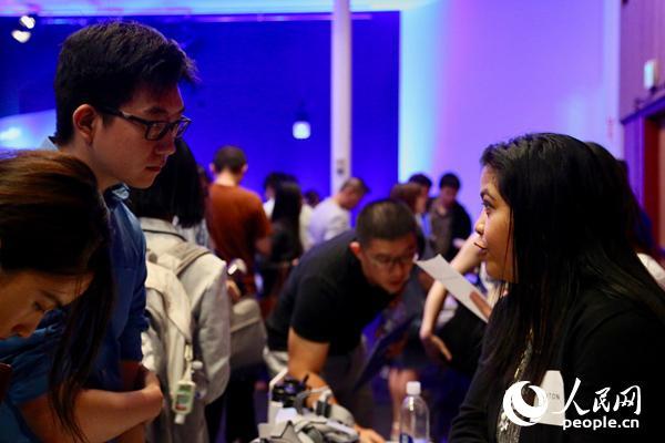 在领英海外人才招聘活动上,一名求职者(左)与企业代表进行交流。人民网张洁娴摄