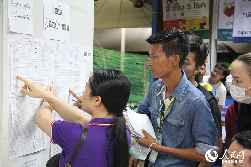 在普吉瓦奇拉医院,志愿者正在帮助中国游客家属确认亲友信息。(人民网记者 张志文 摄)