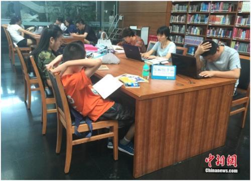 资料图:图书馆内部门儿童正认真阅读,一旁标识提醒读者保持安静。杨雨奇 摄