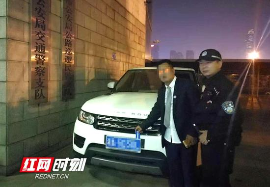 民警将套牌车主带回交警大队调查。